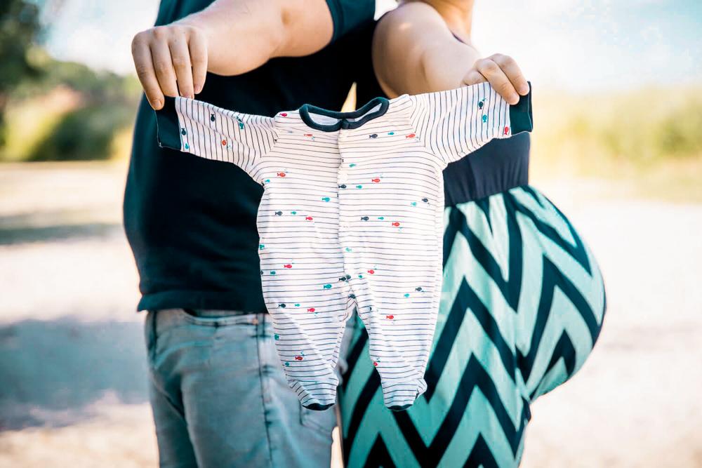 Mann und schwangere Frau stehen Rücken an Rücken und präsentieren den ersten Strampfer für ihr Baby.