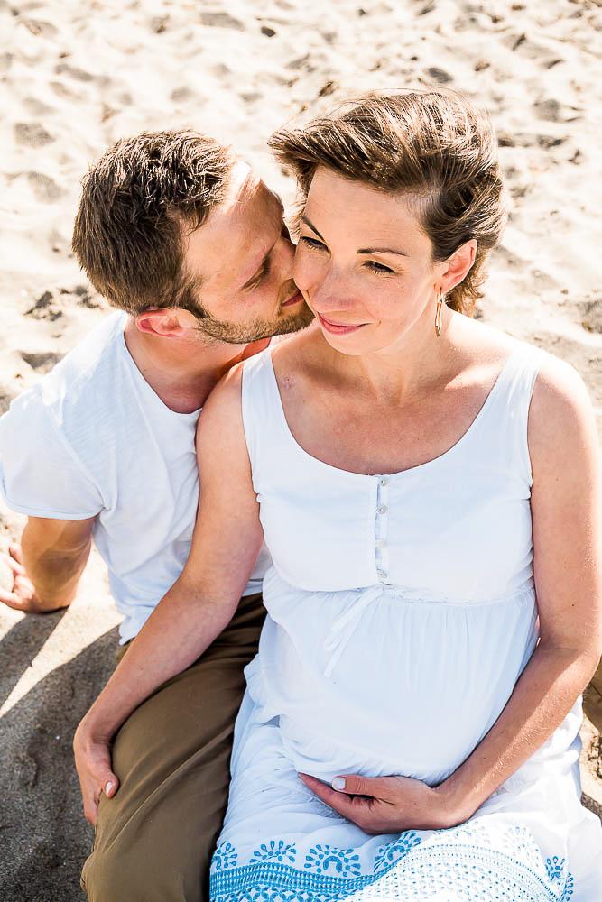 Mann küsst schwangere Frau am Strand.