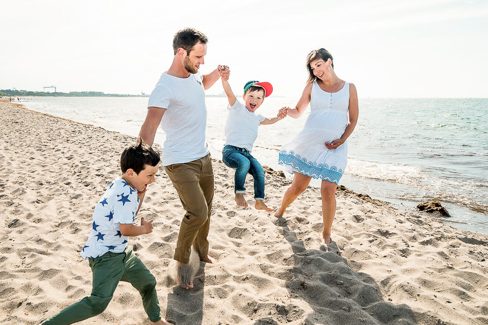 Schwangere Familie lässt Kinder am Strand von Markgrafenheide fliegen.