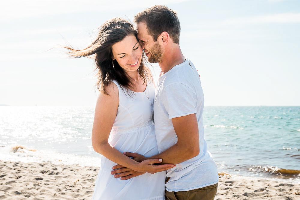 Paar mit weißer Kleidung steht verliebt am Strand von Markgrafenheide, die Haare wehen im Wind.