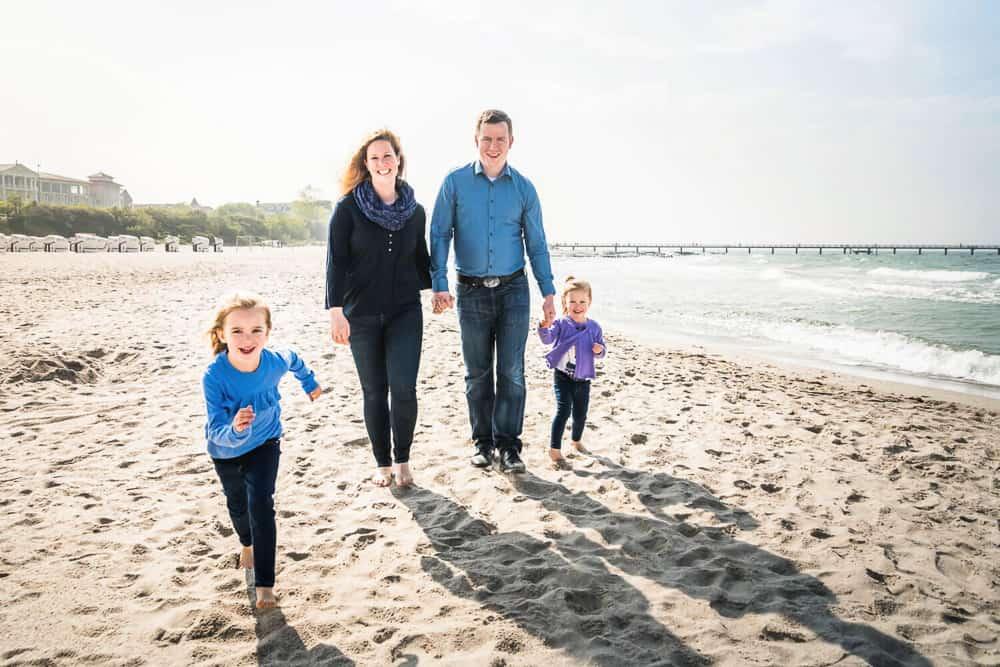 Vierköpfige Familie läuft am Strand entlang.