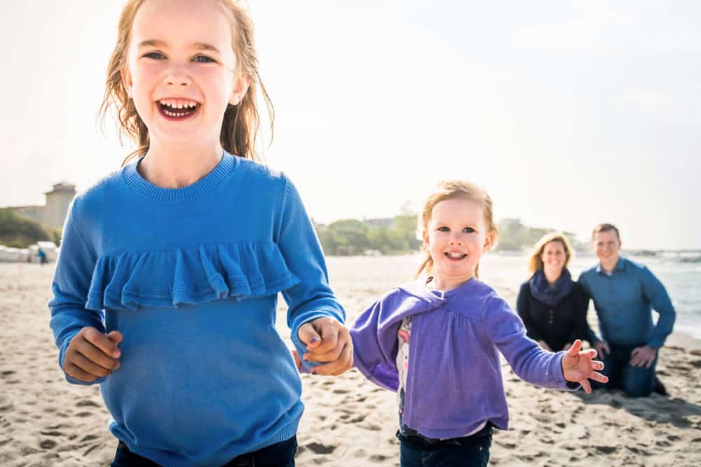Eltern sitzen am Strand und ihre Töchter laufen voller Freude auf die Kamera zu