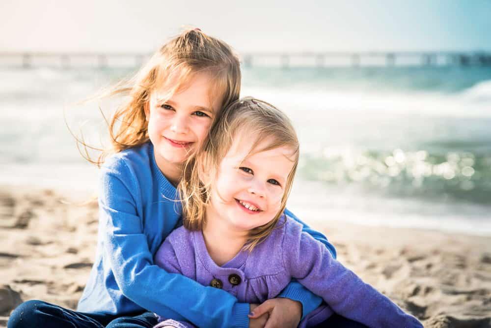 Große Schwester umarmt ihre kleine Schwester am Strand von Kühlungsborn