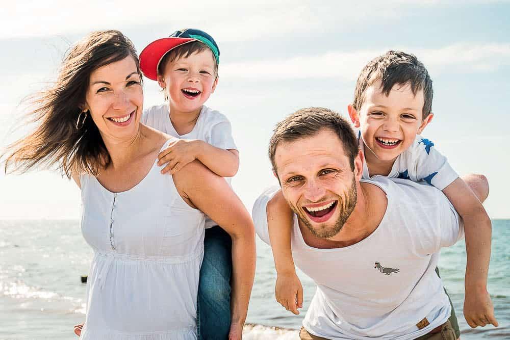 Eltern haben ihre Söhne auf dem Rücken und grinsen alle in die Kamera