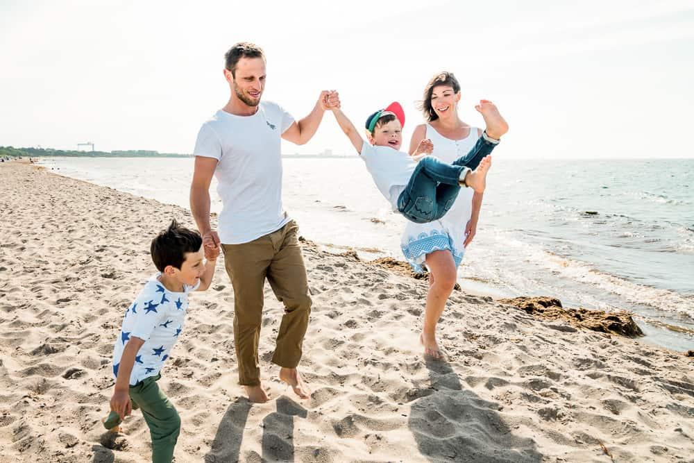 Familie am Strand lässt ihren Sohn fliegen.