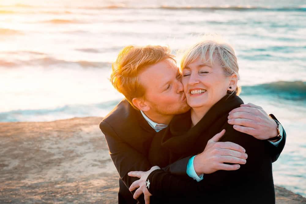 Erwachsener Sohn gibt seiner Mama einen Kuss auf die Wange und sie umarmen sich am Meer.