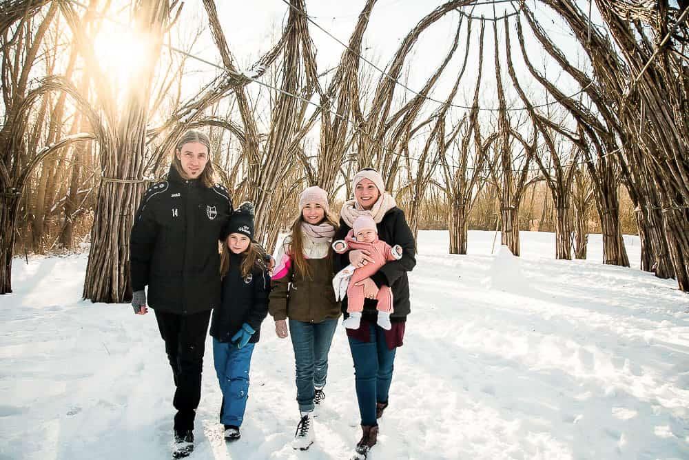 Familie läuft unter einem Weidendom entlang bei Sonnenschein und Winterlandschaft