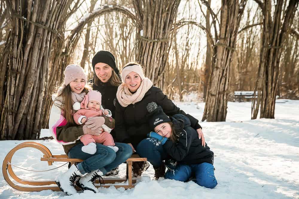 Familie sitzt unter einem Weidendom voller Schnee auf einem Schlitten.