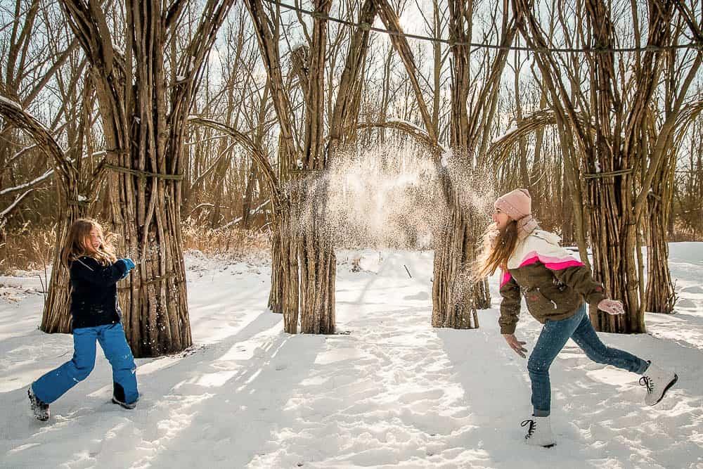 Bruder oder Schwester machen eine Schneeballschlacht im Weidendom