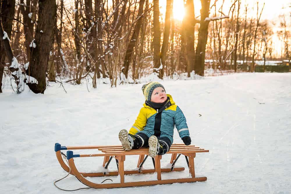 Kleinkind sitzt auf einem Schlitten bei Sonnenuntergang