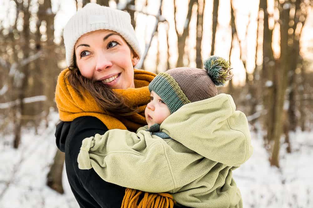 Mama hält ihr Baby im Arm im Winter mit Schnee im Sonnenuntergang im Wald.