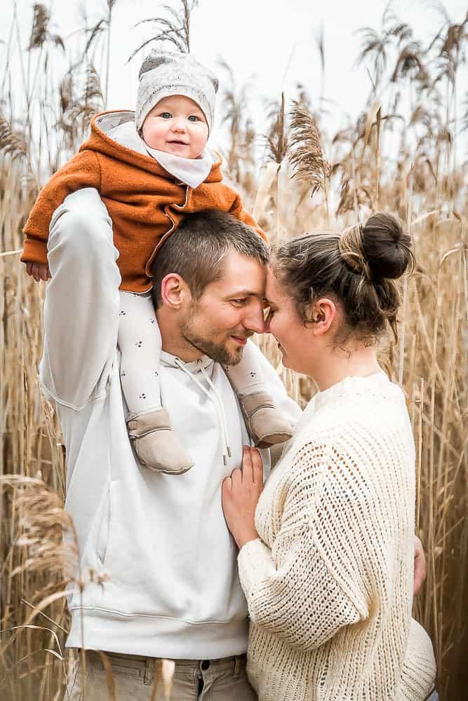 Einjährige Tochter sitzt auf den Schultern von Papa. Mama und Papa stehen sich dicht gegenüber mit Stirn an Stirn.