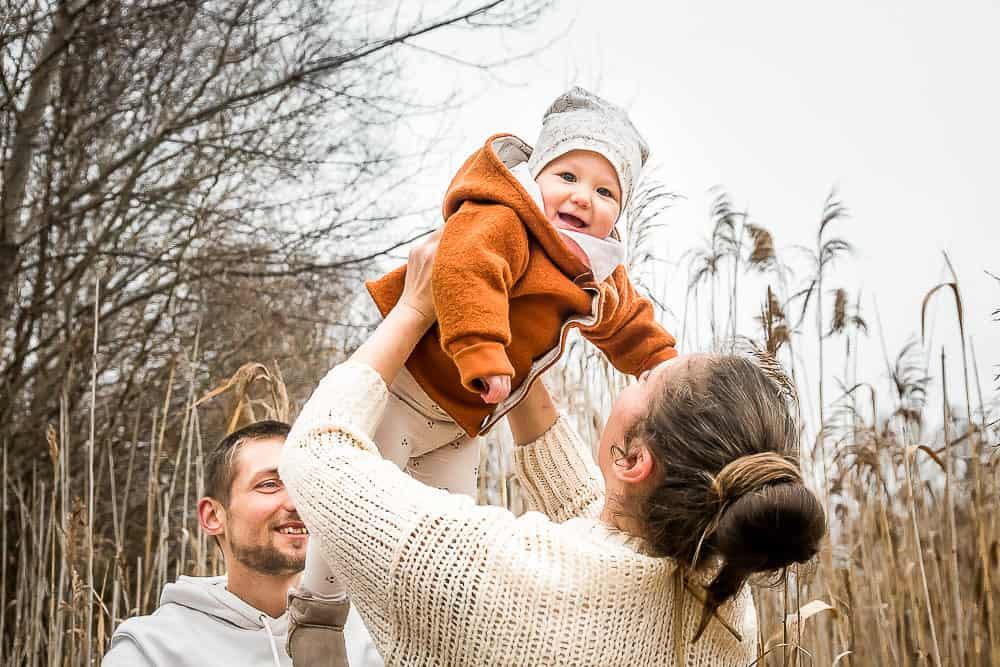 Mama hält einjährige Tochter hoch in die Luft