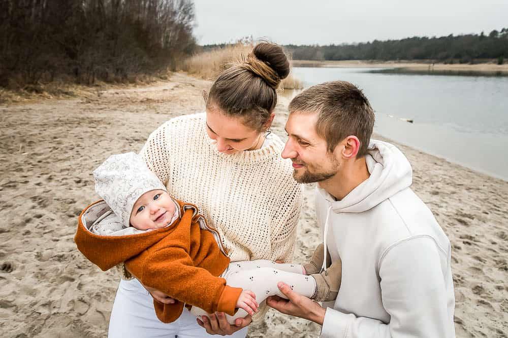 Eltern halten einjährige Tochter im Arm am See