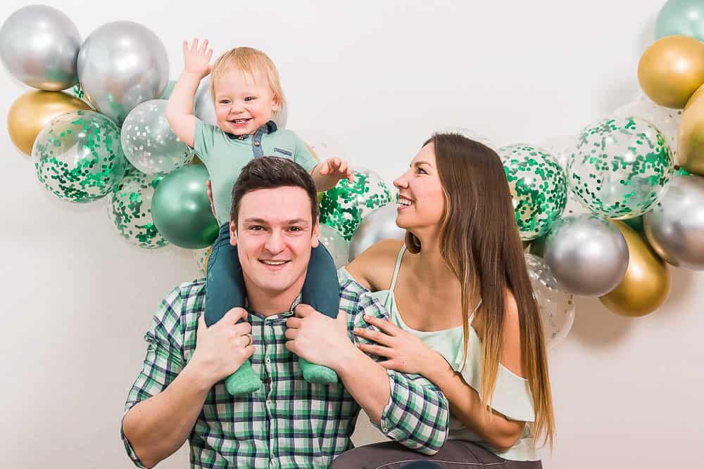 Familie vor Luftballon-Girlande. Einjähriger Sohn sitzt auf den Schultern von Papa.