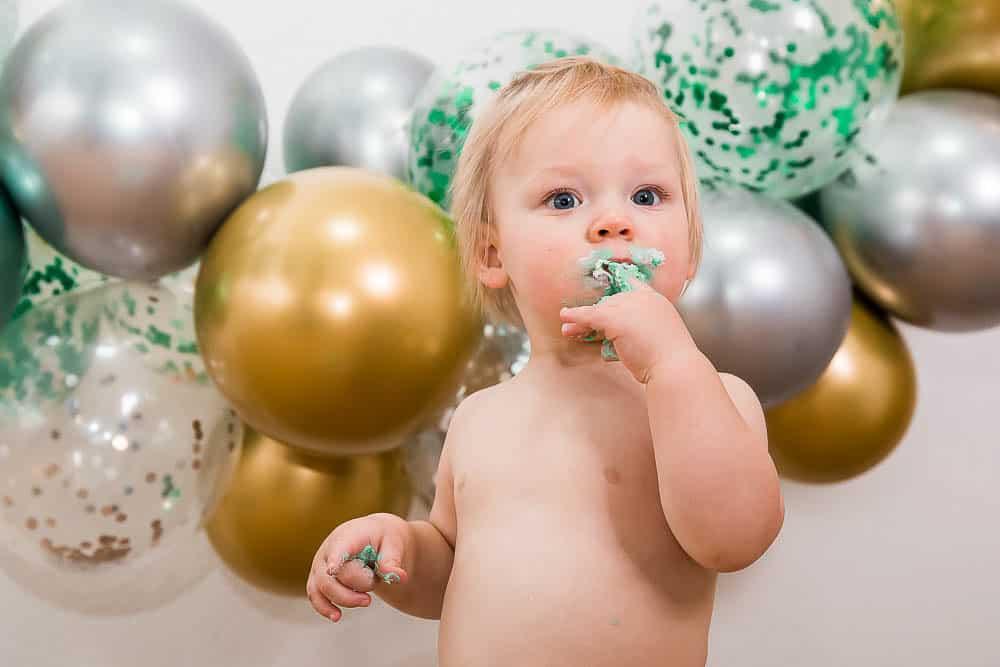 Kleinkind vor Luftballons beim Kuchen essen.