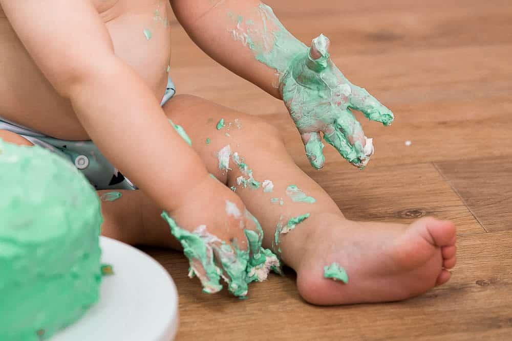 Nahaufnahme von Händen, Beinen und Füßen beim Cake-Smash-Fotoshooting