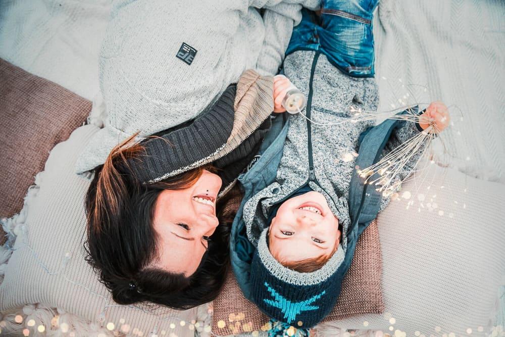 Mama und Sohn liegen auf einer Decke, kuscheln und Junge hält Lichterkette in der Hand.