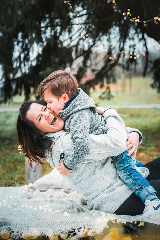 Sohn gibt seiner Mama einen Kuss, im Hintergrund eine Tanne und überall Lichterketten.