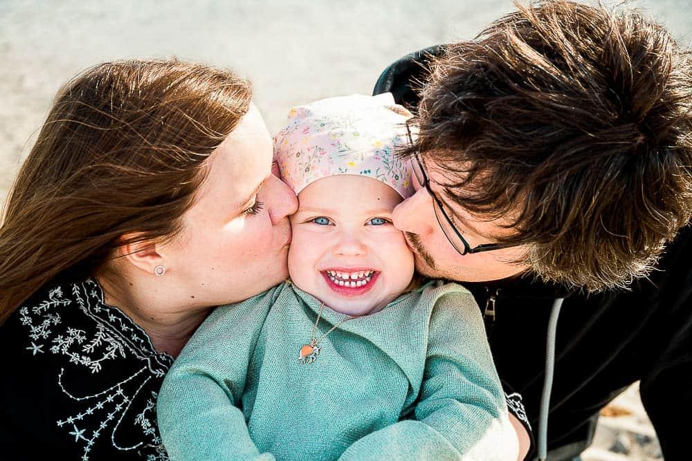 Eltern geben ihrer Tochter einen Kuss auf die Wange, das Mädchen freut sich sehr darüber.