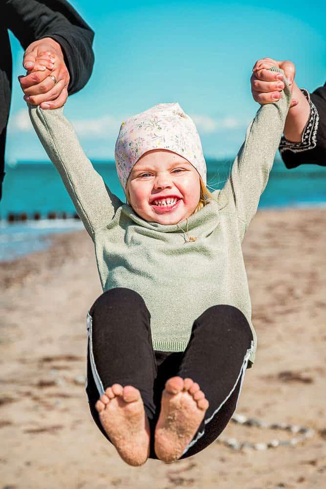 Eltern lassen ihre Tochter am Strand zwischen ihnen fliegen