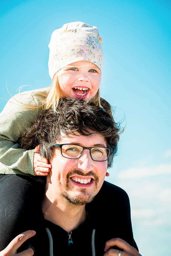 Mädchen auf den Schultern von Papa bei Sonnenschein