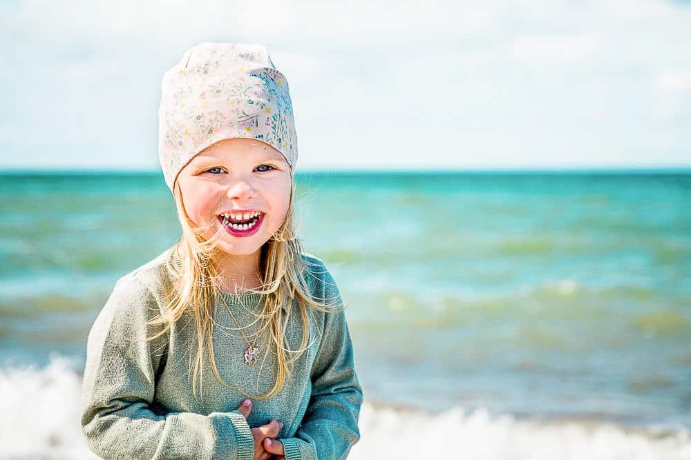 Freudiges Portrait von dreijährigem Mädchen mit Ostsee im Hintergrund
