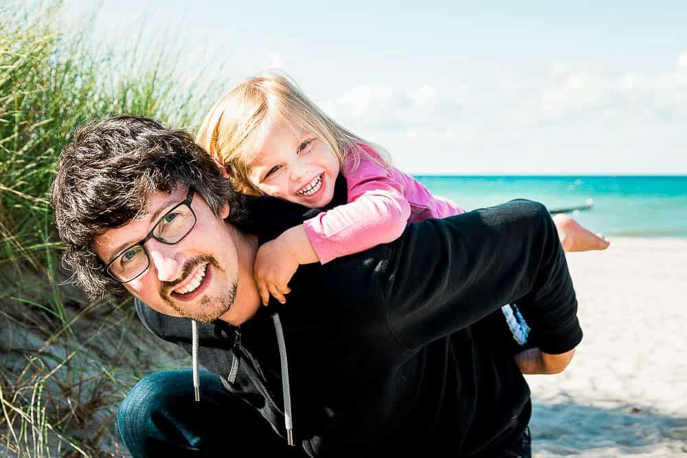 Kind ist auf dem Rücken vom Papa am Strand.