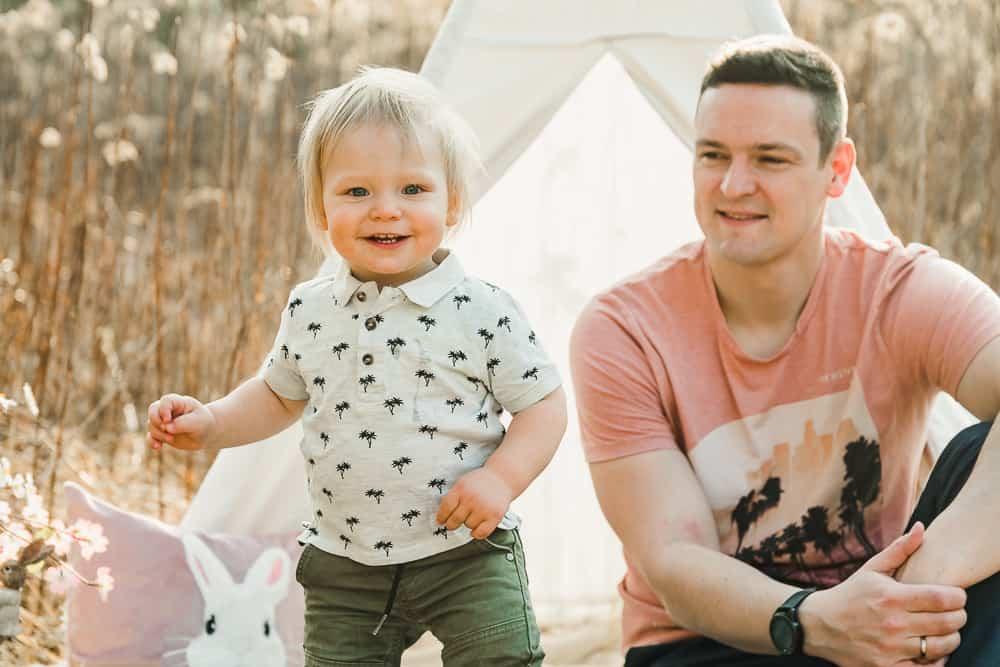 Kleinkind steht neben Papa im Feld mit Tipi-Zelt