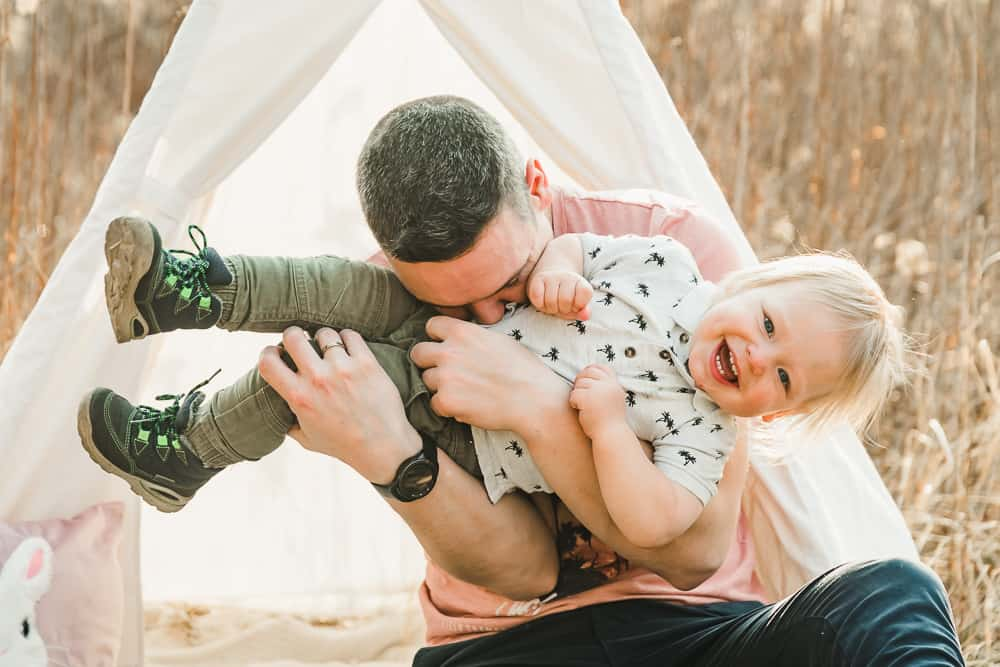 Papa kitzelt seinen Sohn ab.