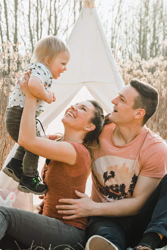 Familie sitzt im Feld vor einem Tipi-Zelt und lässt einjährigen Sohn fliegen.