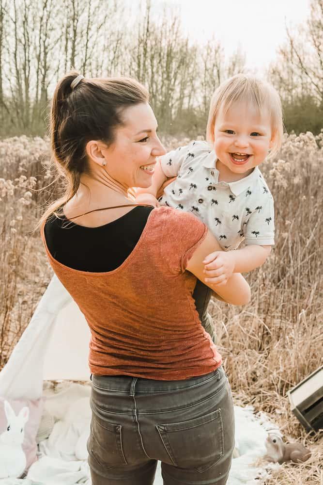 Mama hält Sohn auf ihrem Arm im Feld