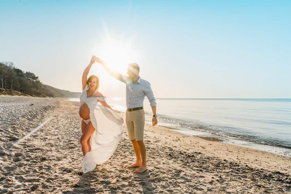 Babybauchfotos bzw. Schwangerschaftsfotos von den werdenden Eltern am Strand von Warnemünde an der Ostsee zu Sonnenuntergang. Echte, natürliche und authentische Fotos für wunderschöne Erinnerungen als Familie.